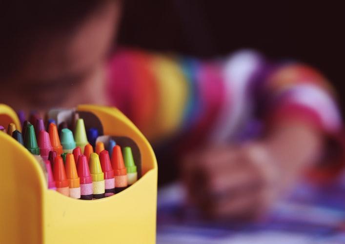 Em primeiro plano, observamos uma caixa com lápis coloridos. Ao fundo, desfocado, uma criança desenhando.