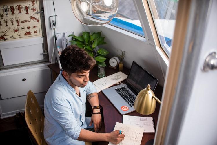 homem jovem em mesa de estudos.
