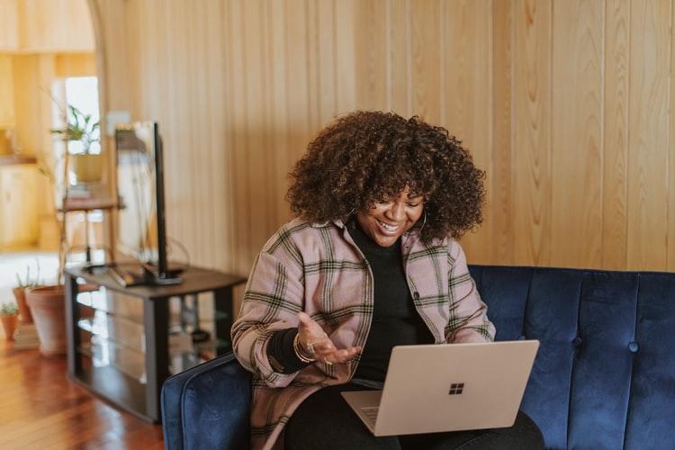 mulher jovem rindo enquanto mexe em um notebook.
